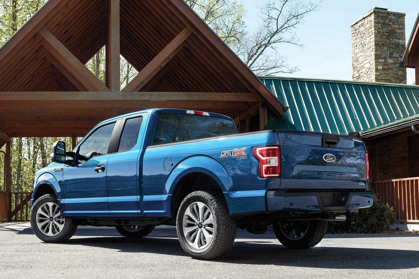 Rear 3/4 angle of Lightning blue Ford F-150 under wooden entrance